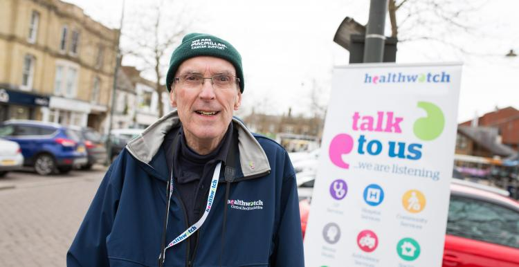 Man wearing a winter hat and stood in front of a Healthwatch banner