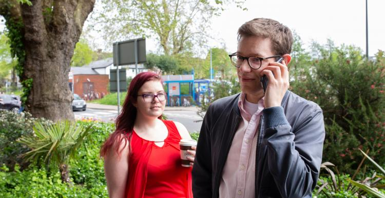 Man talking on his mobile phone, whilst a woman watches him