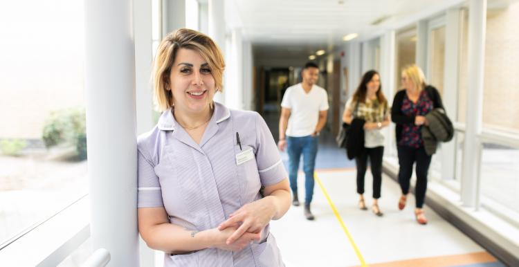 Nurse standing in a corridor with three members of the public