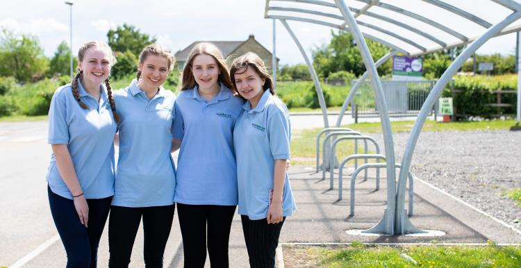 Four girls standing outside a bike shed with their arms round each other