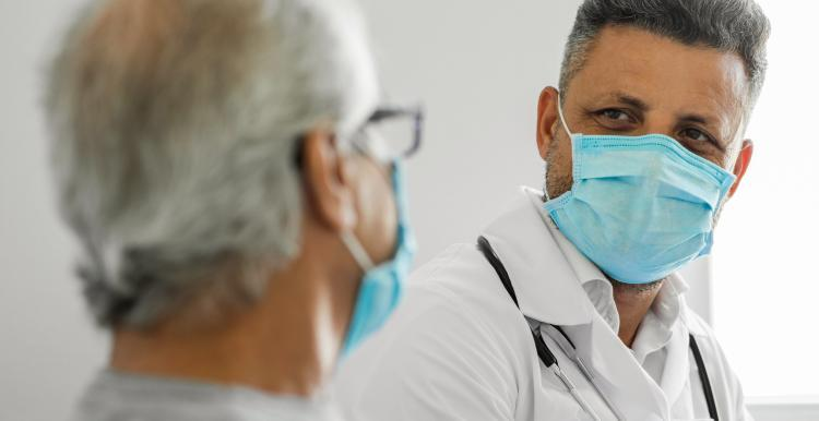 Doctor talking to a senior patient at home