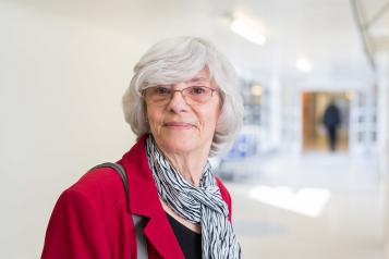 Woman stood in a hospital corridor smiling at the camera