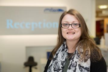 Woman stood in front of a reception sign smiling at the camera