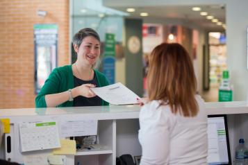 woman stood at a reception desk talking to the lady behind the counter