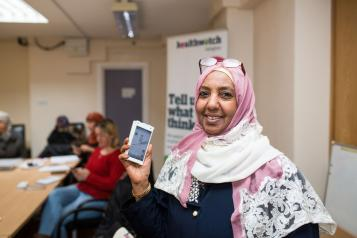 Young lady holding a phone and smiling at the camera