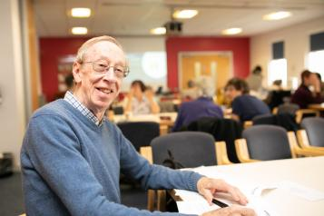 Man sitting in a busy canteen, smiling at the camera