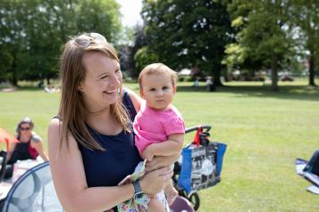 Mother holding her baby in a park green