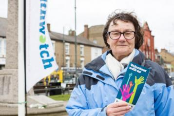 Healthwatch Volunteer in front of banner