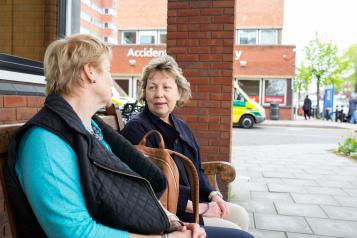 Two women sitting on a bench chatting outside a hospital
