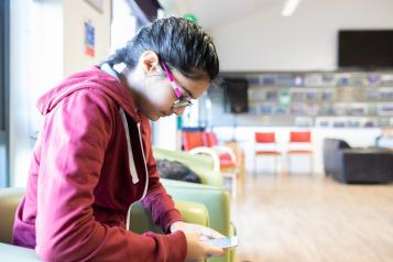 Young person using their phone in a waiting room