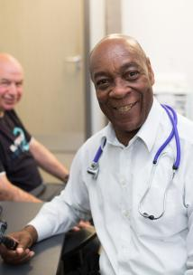 GP smiling at the camera with a patient in the background